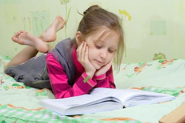 Kleines kindermädchen, das auf einem bett liegt und ein buch liest