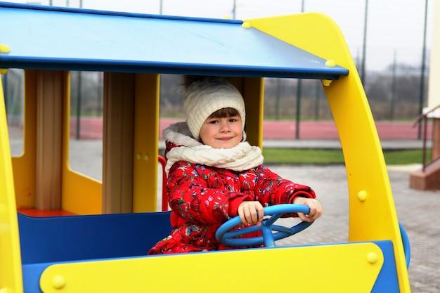Kleines kindermädchen, das auf spielplatz im freien im auto spielt