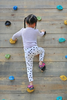 Kleines kindermädchen, das draußen auf freiem klettern auf der hölzernen wand des spielplatzes versucht.