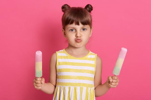 Kleines kindermädchen, das eiscreme in beiden händen hält, mit abgerundeten lippen, weibliches kind mit zwei haarknoten lokalisiert über rosenwand.