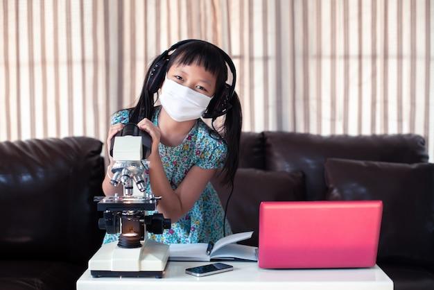 Kleines kindermädchen, das gesichtsmaske und kopfhörer trägt, die online lernen, indem laptop und mikroskop zu hause fernunterricht verwendet werden