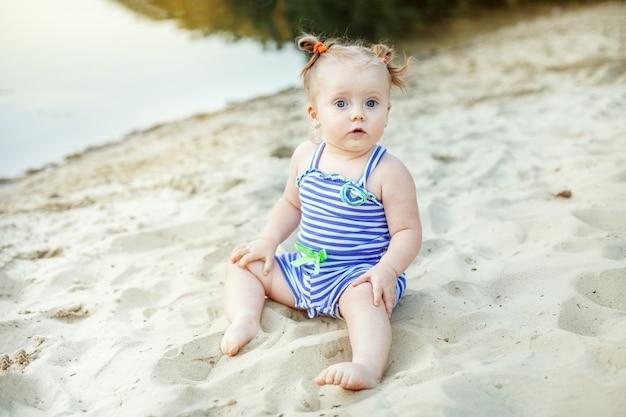 Kleines kindermädchen, das im sand spielt. kindheit, freizeit und lebensstil.