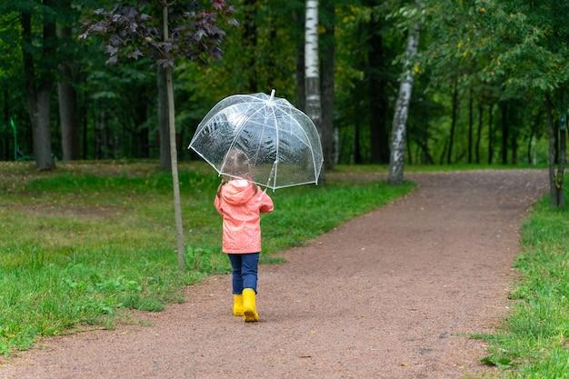 Kleines kindermädchen, das in regenstiefeln im regen geht