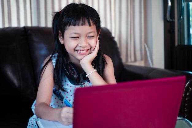 Kleines kindermädchen, das zu hause auf laptop lernt, online-bildungskonzept