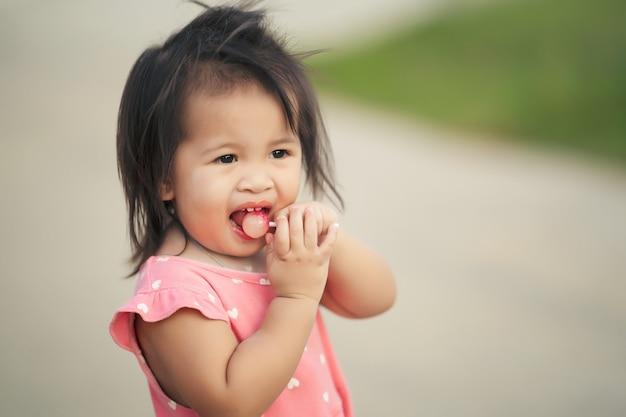 Kleines kindermädchen genießt das essen der lutschersüßigkeit