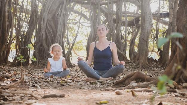 Kleines kindermädchen mit ihrer jungen mutter, die zusammen unter großem banyanbaum meditiert