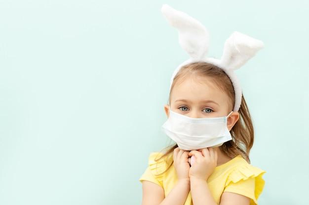 Kleines kindermädchen mit traurigen blauen augen, die hasenohrenstirnband und medizinische schutzmaske tragen, die farbige eier halten