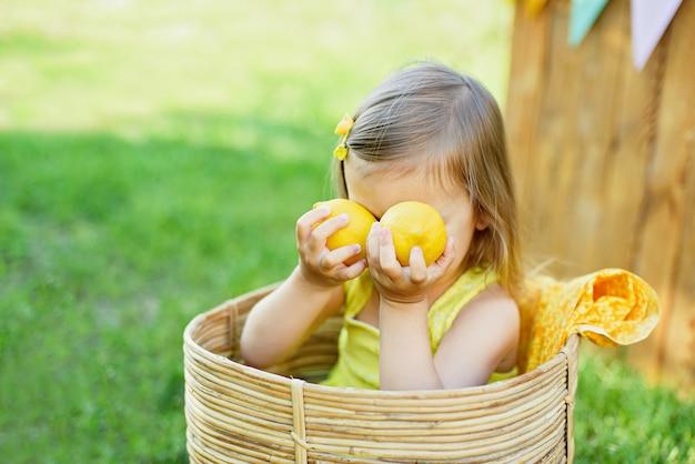 Kleines kindermädchen mit zitronen am limonadenstand im park. porträt des lustigen babys im korb mit früchten
