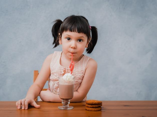 Kleines kindermädchen trinkt heiße schokolade oder kakao mit keksen durch eine cocktailröhre auf einem grau