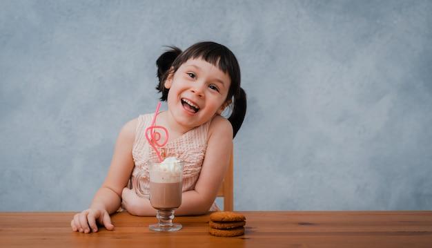 Kleines kindermädchen trinkt heiße schokolade oder kakao mit keksen durch eine cocktailröhre.
