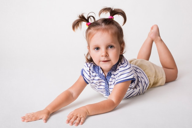 Kleines kleines entzückendes weibliches kind liegt auf weißem hintergrund, hat zwei pferdeschwänze, gekleidet in gestreiftem t-shirt und shorts