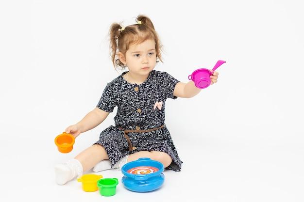 Kleines kleinkind 2 jahre alt, das küchenspielzeug auf weißem hintergrund spielt