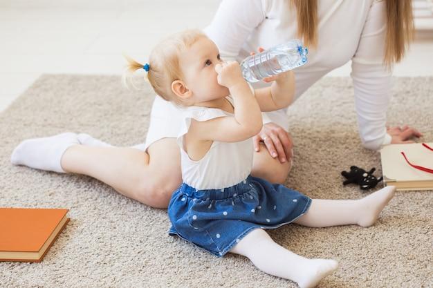 Kleines kleinkind-baby mit einer flasche mineralwasser zu hause. kinder- und familienkonzept.