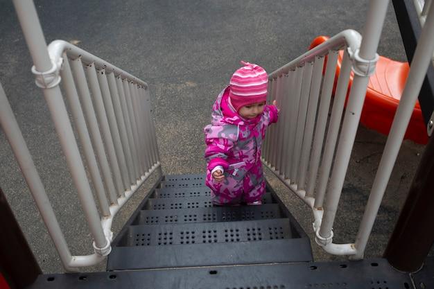 Kleines kleinkind im warmen winteroverall spielt auf dem spielplatz. weicher fokus