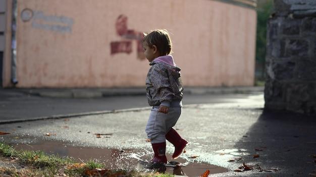 Kleines kleinkind in den roten regenstiefeln, die in der pfütze spielen. fröhliche herbstaktivität