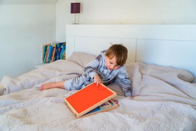 Kleines kleinkind spielt auf dem bett in einem hölzernen magnetkonstrukteur, vorschulkind, das zu hause lernt, mosaik zu machen. frühe entwicklung