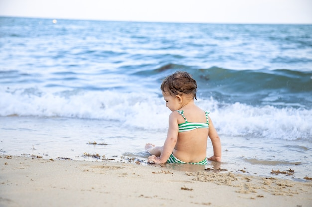 Kleines kleinkindmädchen, das am strand sitzt und die wellen betrachtet. rückansicht.