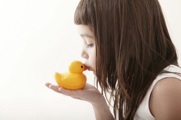 Kleines kleinkindmädchen, das eine gelbe badente küsst