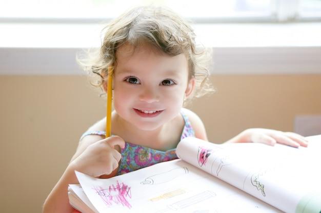 Kleines kleinkindmädchen, das in der schule schreibtisch schreibt