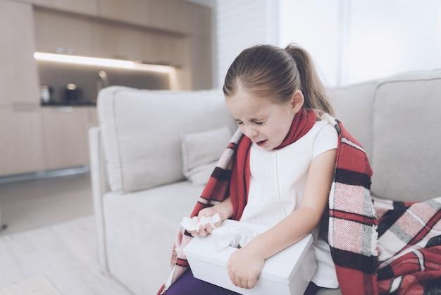 Kleines krankes mädchen sitzt auf einer weißen couch, die in einem roten schal eingewickelt wird.