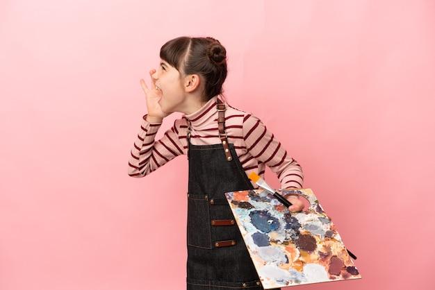 Kleines künstlermädchen, das eine auf rosafarbenem hintergrund isolierte palette hält und mit weit geöffnetem mund zur seite schreit