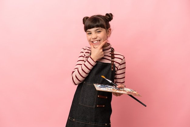 Kleines künstlermädchen, das eine palette lokalisiert auf rosa glücklich und lächelnd hält
