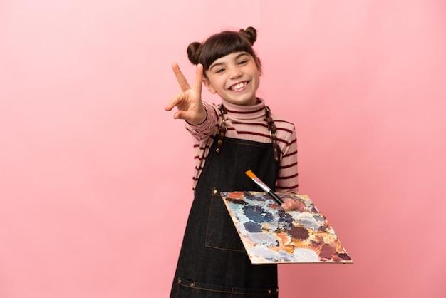 Kleines künstlermädchen, das eine palette lokalisiert auf rosa lächelnd hält und siegeszeichen zeigt