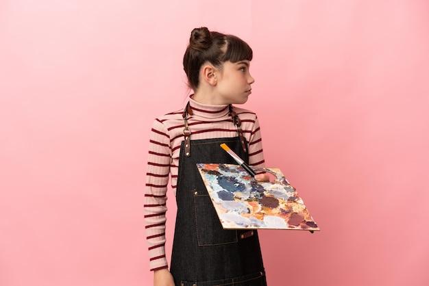 Kleines künstlermädchen, das eine palette lokalisiert, die auf rosa lokalisiert schaut