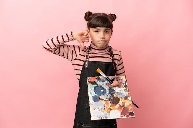 Kleines künstlermädchen, das eine palette lokalisiert, die auf rosa lokalisiert zeigt daumen unten mit negativem ausdruck