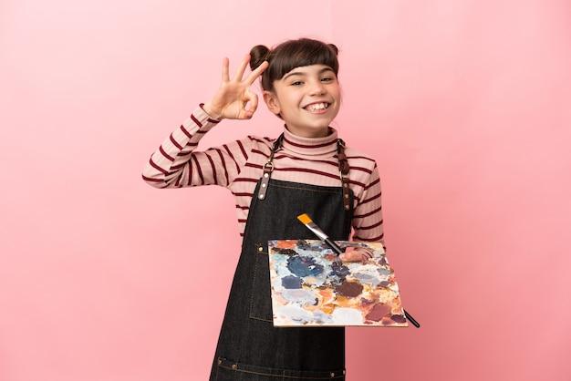 Kleines künstlermädchen, das eine palette lokalisiert, die auf rosa lokalisiertes ok zeichen mit den fingern hält