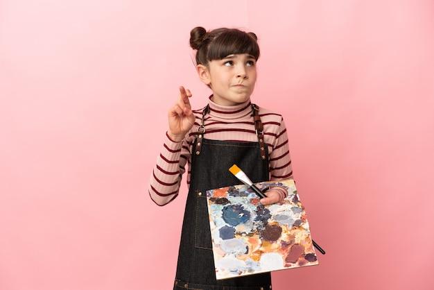 Kleines künstlermädchen, das eine palette lokalisiert hält, die mit den fingern kreuzt und das beste wünscht