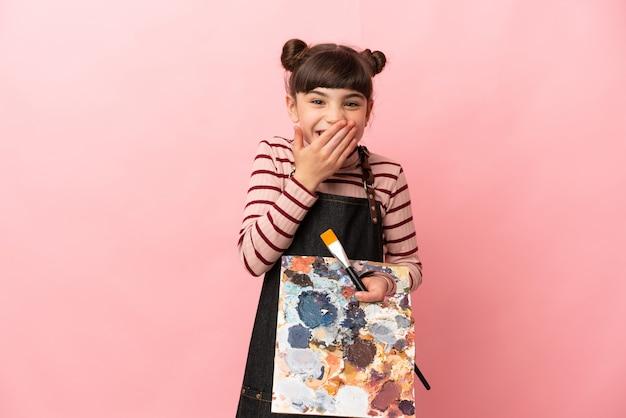 Kleines künstlermädchen, das eine palette lokalisierte lächelnde bedeckende mund mit hand hält