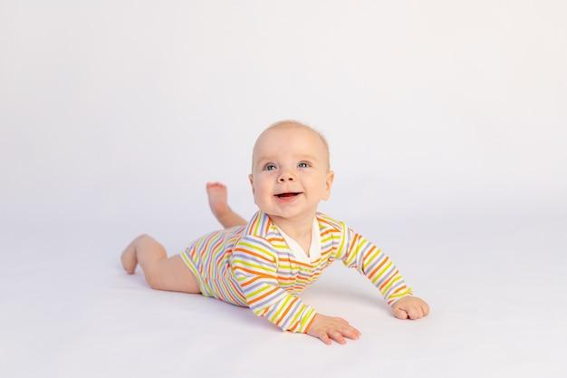 Kleines lächelndes baby 6 monate alt liegt in einem hellen body. ein gesundes glückliches kind.