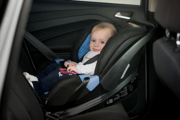Kleines lächelndes baby auf dem rücksitz