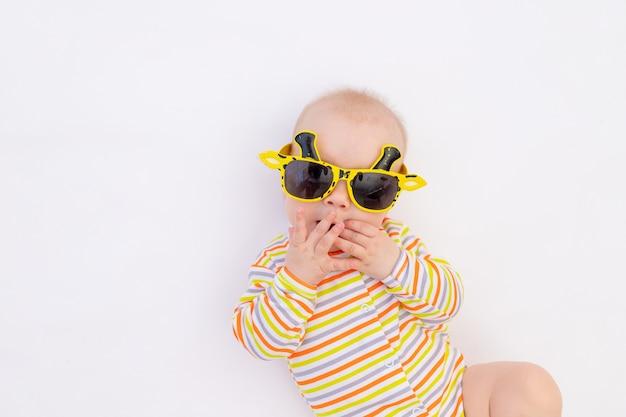 Kleines lächelndes baby, das auf einem weißen isolierten hintergrund in hellen sonnenbrillen liegt