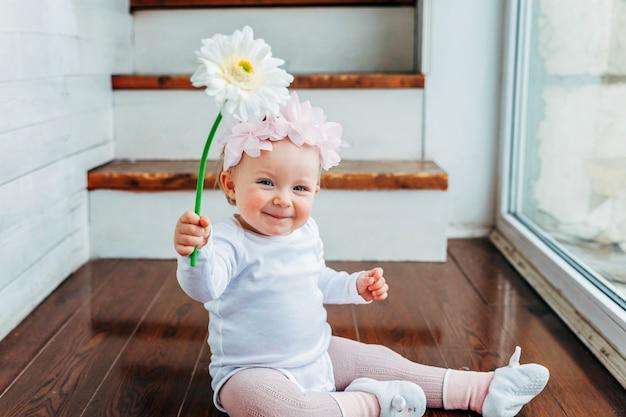Kleines lächelndes baby, das frühlingskranz trägt, der auf boden sitzt und mit gerberablume spielt