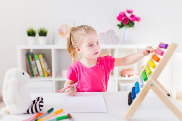 Kleines lächelndes blondes mädchen, das am weißen schreibtisch sitzt und auf den bunten abakus im klassenzimmer zählt. heimunterricht