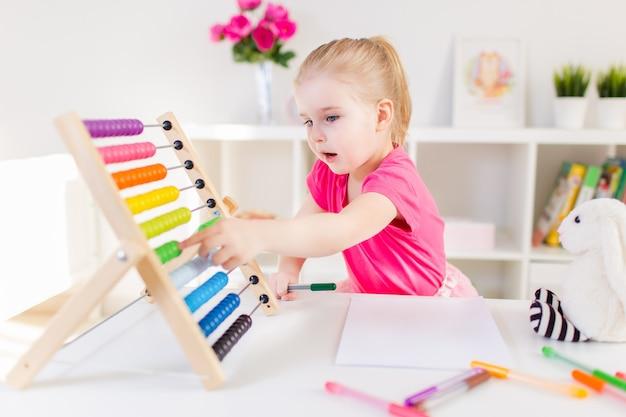 Kleines lächelndes blondes mädchen, das am weißen schreibtisch sitzt und auf den bunten abakus im klassenzimmer zählt. vorschulbildung.