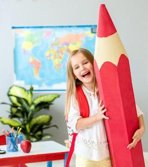 Kleines lächelndes blondes mädchen, das enormen roten bleistift im schulklassenzimmer hält