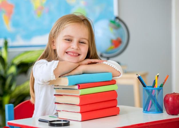 Kleines lächelndes blondes mädchenhändchenhalten auf den büchern im schulklassenzimmer