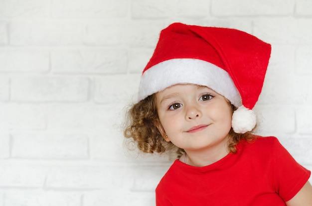 Kleines lächelndes glückliches mädchen im weihnachtsmannhut für frohe weihnachten