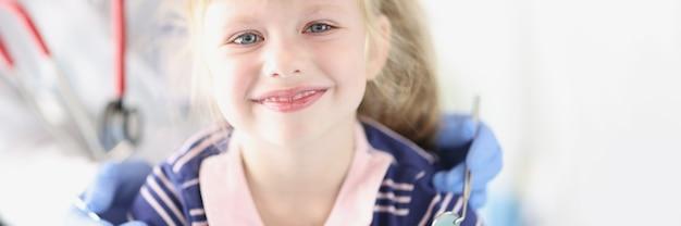 Kleines lächelndes mädchen, das beim zahnarzttermin sitzt
