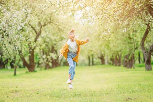 Kleines lächelndes mädchen, das im park spielt