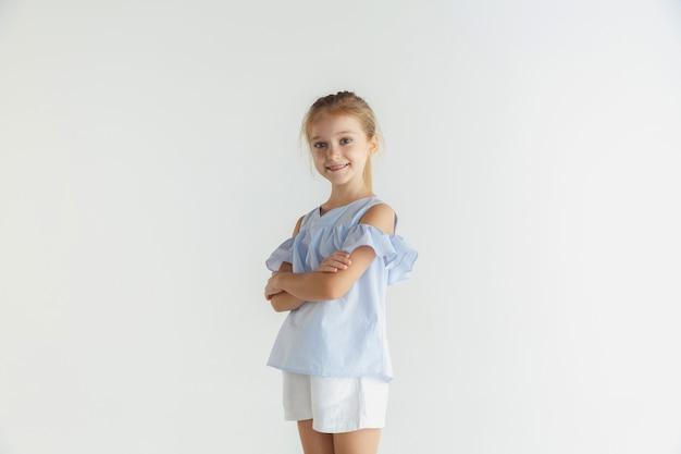 Kleines lächelndes mädchen, das in der freizeitkleidung auf weißem studio aufwirft