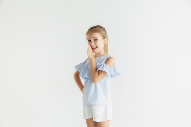 Kleines lächelndes mädchen, das in der freizeitkleidung auf weißer wand aufwirft