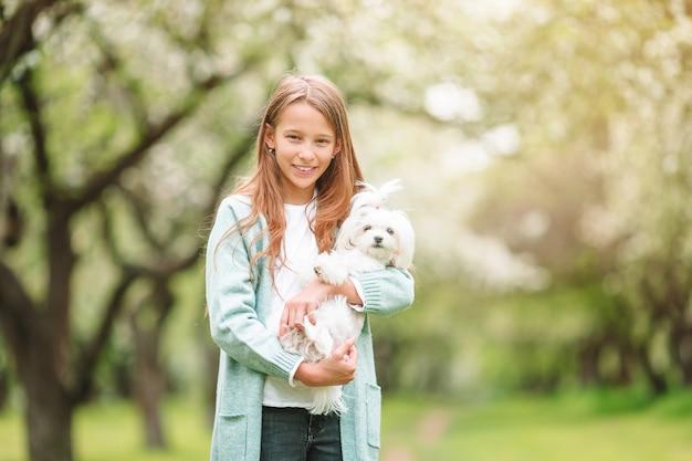 Kleines lächelndes mädchen, das welpen im park spielt und umarmt