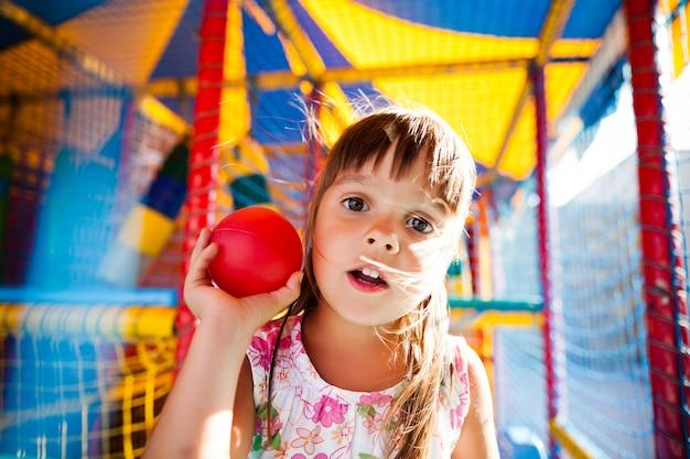 Kleines lächelndes mädchen im kleid, das in den bunten weichen dekorativen bällen im spielzimmer sitzt
