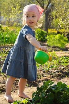 Kleines lächelndes mädchen in einem jeanskleid gießt erdbeerbusch im garten aus einer kinderspielzeuggießkanne.