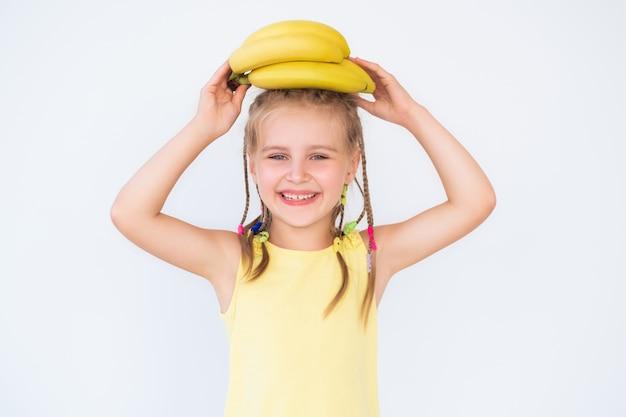 Kleines lächelndes mädchen mit banane im gelben hemd auf weißem hintergrund