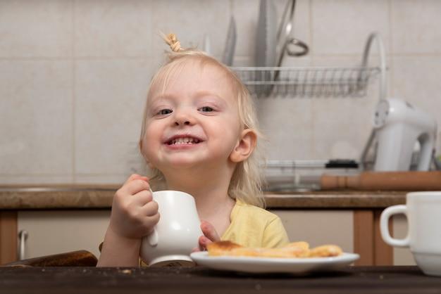 Kleines lächelndes mädchen trinkt eine milch. frühstück mit kind. nettes blondes kind mit tasse in den händen in der küche.